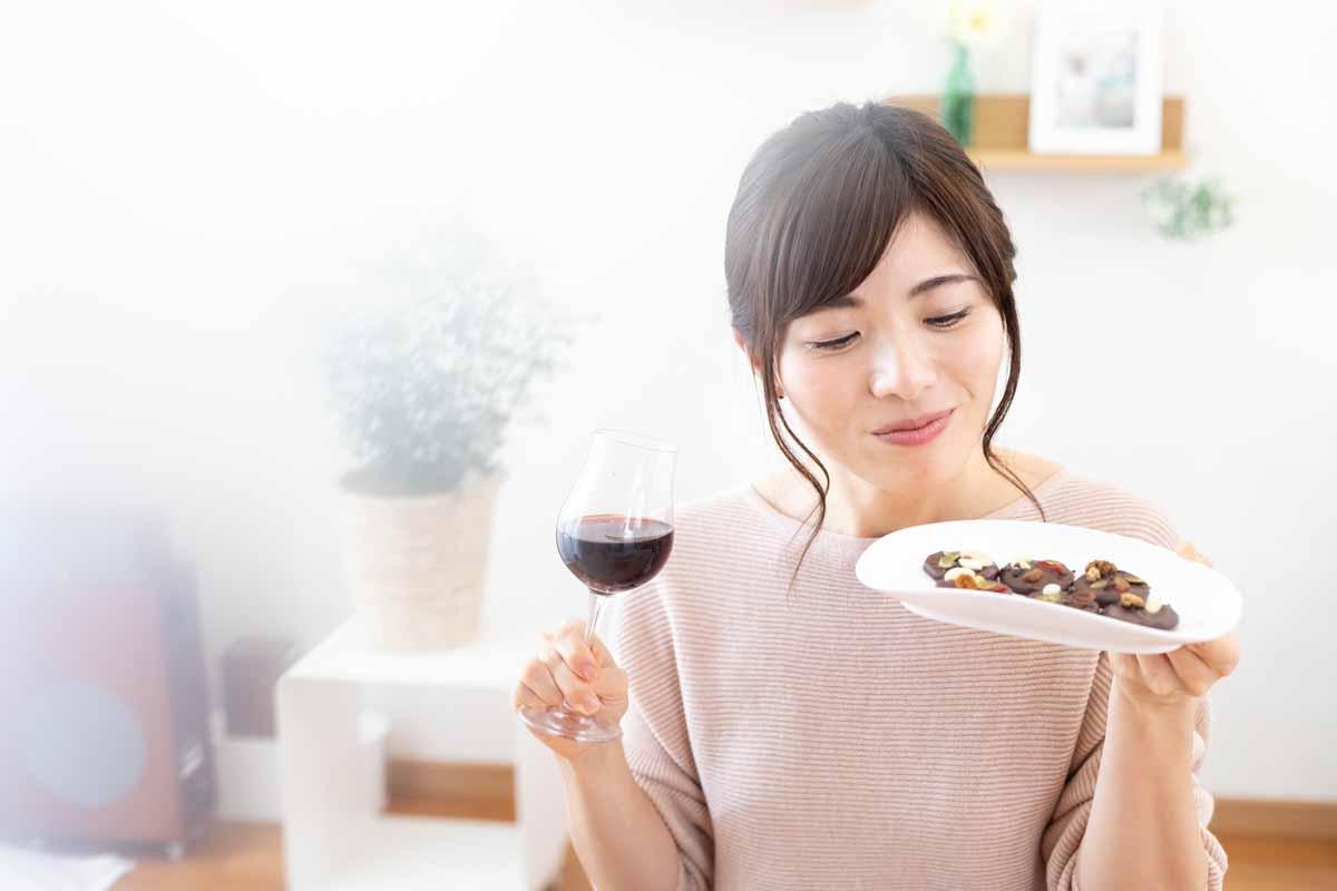 チョコレートとワインを持つ女性
